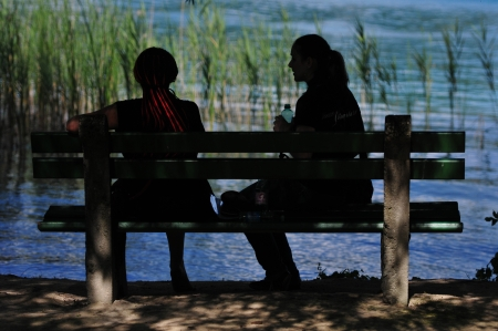two women sitting on a bench and talking Stock Photo