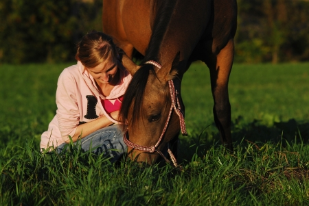 confiding: girl sitting in the pasture beside her grazing horse