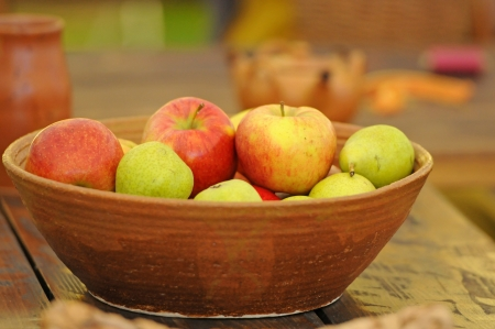 apples in a clay bowl on a wooden table photo