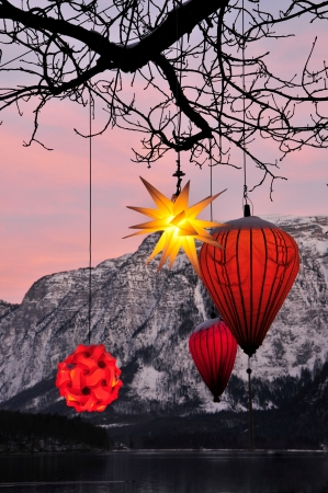 pendular: glowing Chinese lanterns hanging down from a tree with mountains in the background Stock Photo