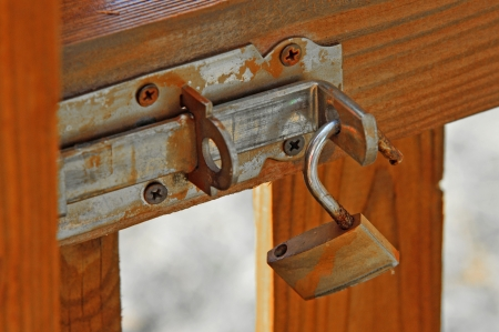 rusty old padlock on a wooden fence photo