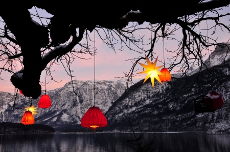 glowing Chinese lanterns hanging down from a tree with mountains in the background Stock Photo