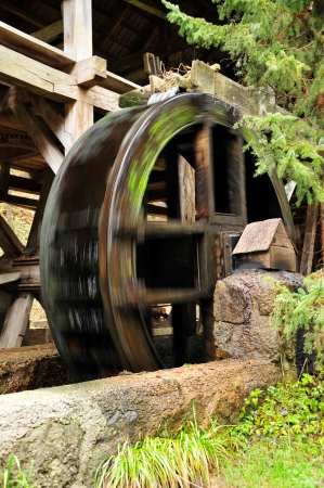 wooden wheel of an ancient water mill in motion Stock Photo
