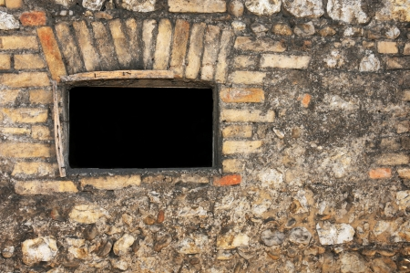 window without glass in an ancient brick wall photo
