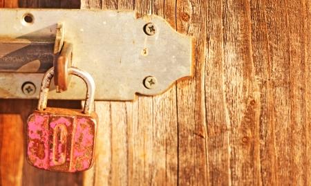 rusty old padlock on a wooden door photo