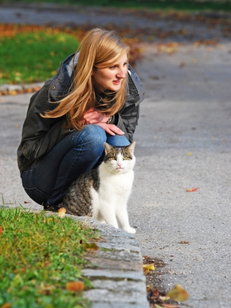 hunker: girl with cat in autumn squatting on the wayside Stock Photo