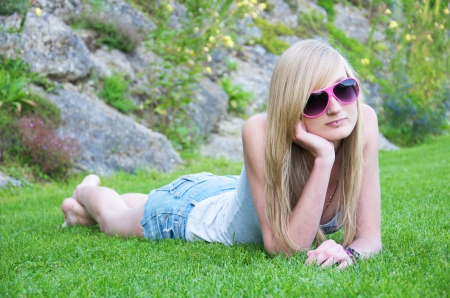 girl with pink sunglasses lying in the grass photo