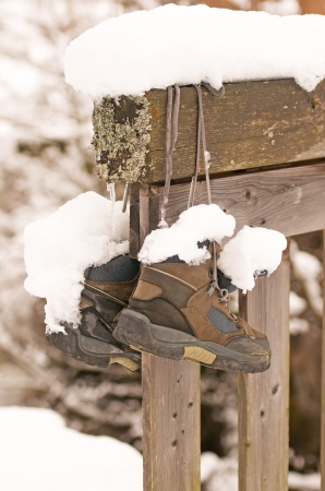 a pair of snow-covered hiking boots hanging on a wooden fence Imagens