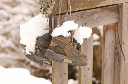 a pair of snow-covered hiking boots hanging on a wooden fence Archivio Fotografico
