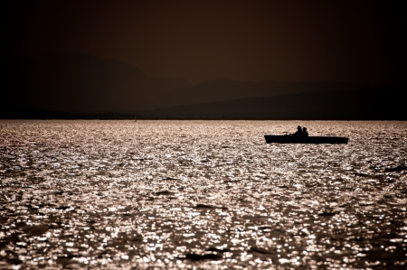 boat with a couple on the ocean at sunset photo