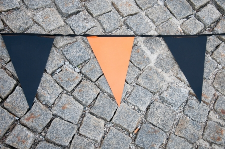 three cornered: orange and blue empty triangular flags on the cobblestone floor