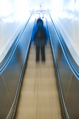 woman on an escalator climbing to the next floor