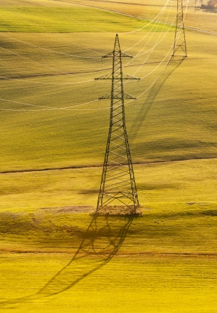 electrical tower over an autumnal rural hill land photo
