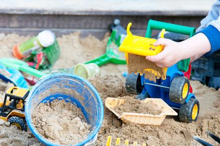 the sandbox: child playing in a sandbox on the playground