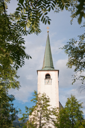 church spire against the cloudy sky surrounded by a tree Stock Photo