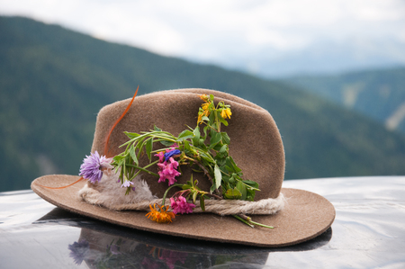 brown felt hat decorated with alpine flowers - austrian mountains in the background