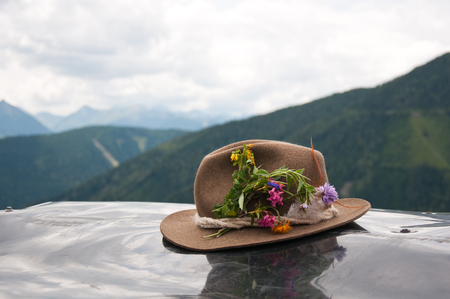 brown felt hat decorated with flowers - austrian mountains in the background - Bachlalm in Filzmoos Salzburg