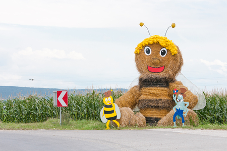 huge comic bee made of straw bales on the wayside Stock Photo