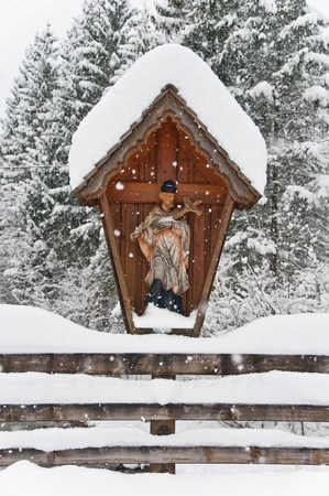 wayside cross on a wooden bridge covered with snow in winter