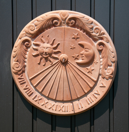 sundial made of clay hanging on a metal door