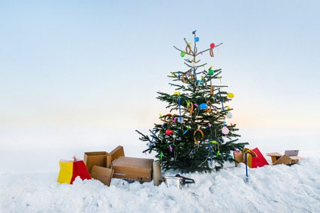 curious open air christmas tree in the snow decorated with sausages, balloons, toilet brushes and clothespins Stock Photo