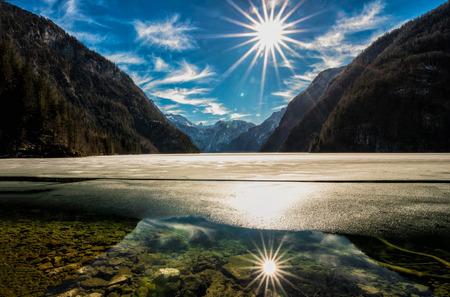 Frozen Königssee with reflecting sunbeams in Berchtesgaden - Germany