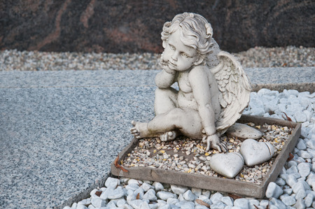angel sitting on a grave with pebble stones