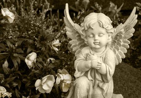 Ángel hecho de arcilla sentado sobre una tumba rodeada de flores - color sepia
