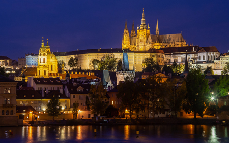 illuminated beautiful Prague at twilight hour with a cloudless blue sky reflecting in the Vltava river - view at the castle