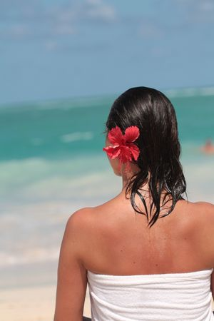 Woman in white towel with brown hairs and red flower standing on the beach
