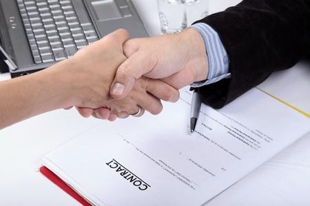contrato de trabajo: Deal. Apret�n de manos del hombre de negocios y la mujer. Documento de contrato en segundo plano