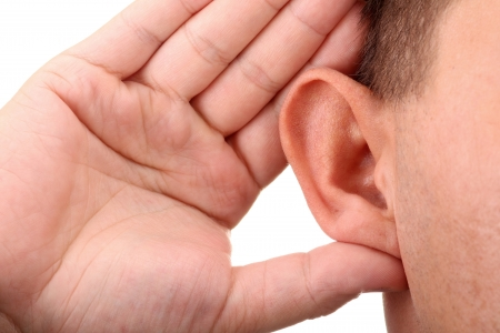 listening ear: What? Closeup for hand on ear