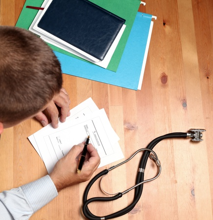 Doctor filling out Prescription. Stock Photo - 10031794