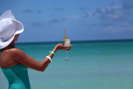 Woman with Pina Colada cocktail relaxin on the Caribbean Sea Stock Photo