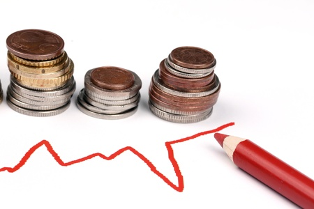 The Ups and Downs. Graph and coins snd red pencil Stock Photo