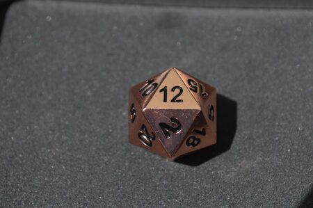 Copper metallic d20 twenty sided dice on foam surface with 12 on top side Archivio Fotografico