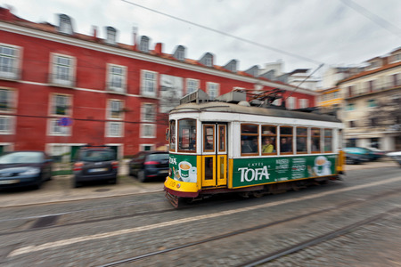 View of the traditional yellow Tram passing through the streets of Lisbon, Portugal providing innercity public transport Editorial