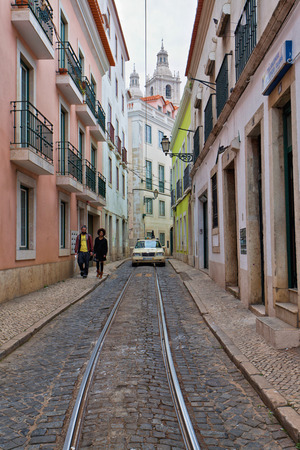 decorative balconies: Street scene in Lisbon city centre with a deserted street running between multistorey historical buildings with decorative balconies and shops at ground level