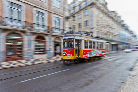 panning shot: Panning shot of a red tram in a street in Lisbon city centre showing motion blur of the background