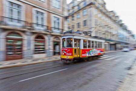 panning shot: Panning tiro di un tram rosso in una strada nel centro di Lisbona mostrando motion blur dello sfondo
