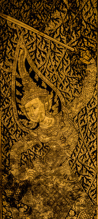 gold colour: Traditional Thailand style art on wall god hang on sword in gold and black colour Stock Photo