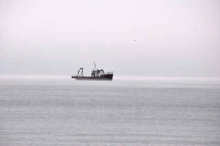 foggy: small fishing ship floating in the fog
