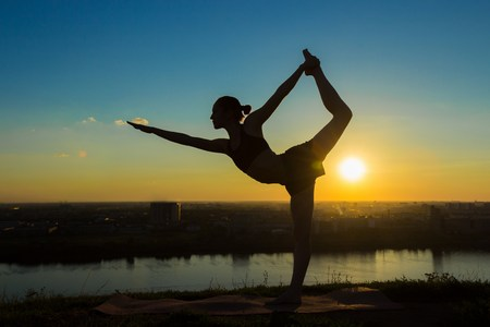 Silhouette of sporty woman practicing yoga in the park at sunset - lord of the dance pose. Sunset light. Freedom, health and yoga concept