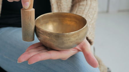tibetan singing bowl: Close up shot of nepal singing bowl in womans hand. Meditation and relax concept
