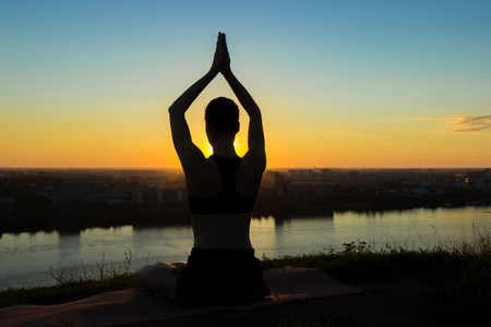 Sporty woman practicing yoga in the park at sunset - sun salutation. Sunset light, golden hour, lens flares. Freedom, health and yoga concept Stock Photo