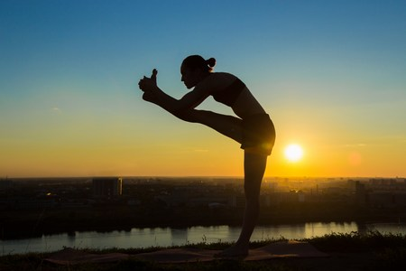 hasta: Silhouette of sporty woman practicing yoga in the park at sunset - utthita hasta padangushthasana. Sunset light, golden hour. Freedom, health and yoga concept