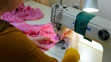 Professional tailor, fashion designer sewing clothes with sewing machine at atelier. Fashion and tailoring concept Stock Photo
