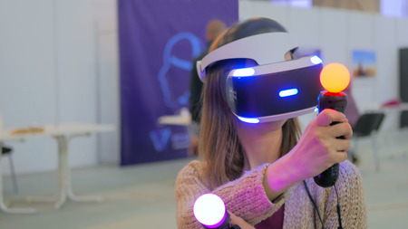 Virtual reality game. Young woman using virtual reality glasses and hand controlers