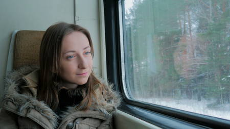Pensive woman relaxing and looking out of a train window. Travel, transport and winter concept