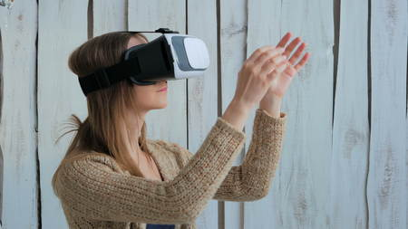 computer simulation: Young woman using Virtual Reality Glasses. Virtual reality mask. VR. White wooden background. Future and technology concept